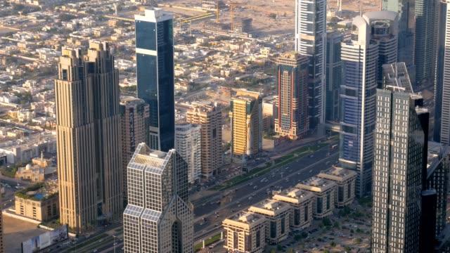 wide road between high modern buildings in dubai city, view from top - cultura del medio oriente video stock e b–roll