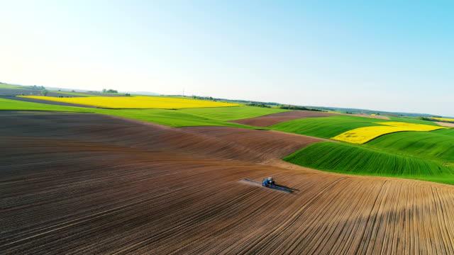 wide shoot of farming, soil fertilization. - trattore video stock e b–roll