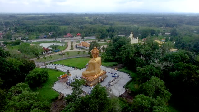 Wide shot aerial drone footage. Flying Phasuttha Thaksin Ming Mongkol Buddha, This Buddha statue is respected. Narathiwat, Thailand.