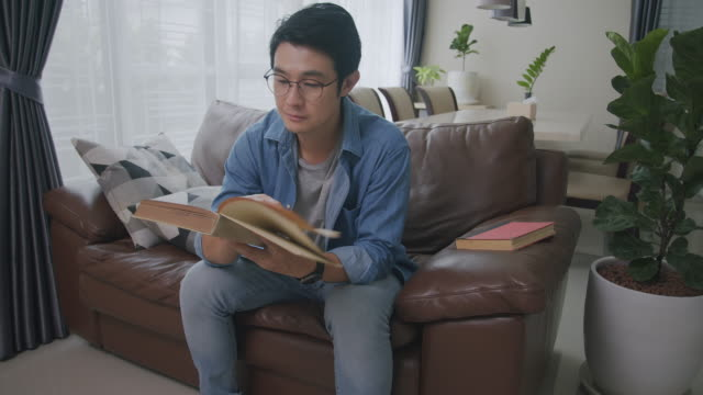 Wide shot POV Asian man reading a book in the living room. Adult male studying history on Analog book while sitting on a sofa. Learning, knowledge, education, relaxing in daily life activities