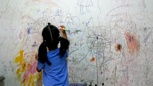 wide shot : child writting on wall of house