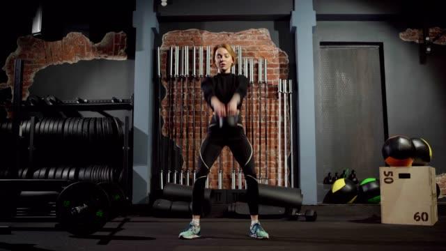 szeroki widok z przodu strzał pasuje sportowe młoda kobieta wykonująca kettlebell swing ćwiczenia robi przysiady i podnoszenia kettlebell nad głową podczas treningu krzyżowego w siłowni - giria filmów i materiałów b-roll
