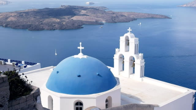 wide shot of a blue church dome and three bells in fira, santorini video