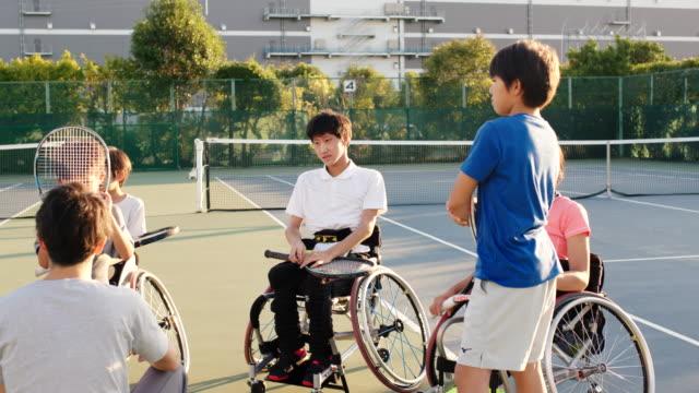 アダプティブテニス選手のチームと話しているコーチのslo moワイドショット - disabilitycollection点の映像素材/bロール