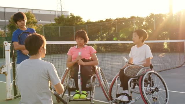 10代のアダプティブテニス選手のチームと話しているコーチのslo moワイドショット - disabilitycollection点の映像素材/bロール