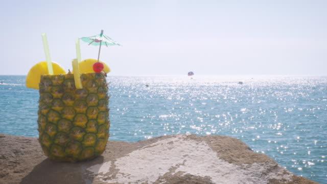 breite schuss von einem cocktail serviert in einer frischen ananas in einem strandresort in 4k - spring break stock-videos und b-roll-filmmaterial