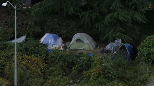Wide shot of a homeless village of tents in the trees in Portland, Oregon