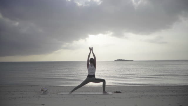 Wide shot of a millennial-aged women practicing yoga on a sandy beach at sunset Wide shot of a millennial-aged women practicing yoga on a sandy beach at sunset mindfulness stock videos & royalty-free footage