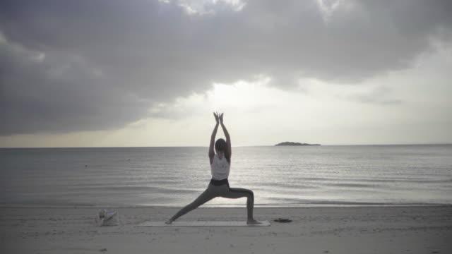 일몰에 모래 해변에서 요가를 연습하는 밀레니엄 세 여성의 넓은 샷 - mindfulness 스톡 비디오 및 b-롤 화면