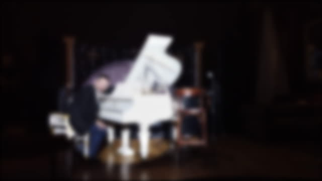 vídeos de stock e filmes b-roll de wide shot of a pianist performing his own music on club interior background. - living room background