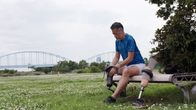Wide shot of a senior adaptive athlete affixing his running blade Wide shot of a senior adaptive athlete affixing his running blade. Shot in 4K. 60 FPS retimed to 23.976 FPS. Osaka, Japan prosthetic equipment stock videos & royalty-free footage