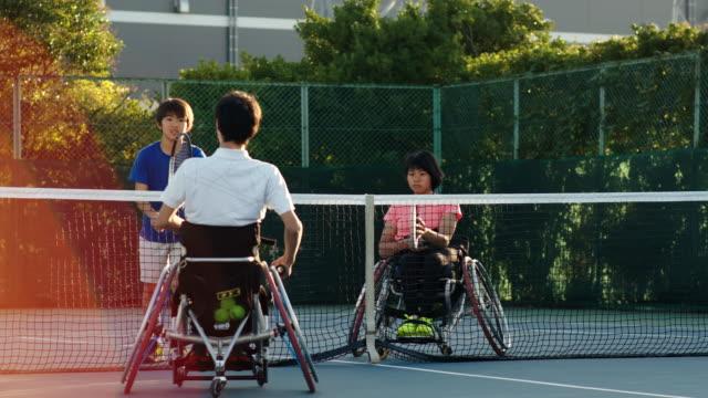 センターコートを話す適応テニス選手のチームのslo moワイドショット - disabilitycollection点の映像素材/bロール