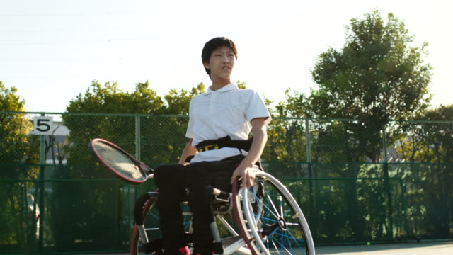 テニスをしている車椅子の10代の適応アスリートのslo moワイドショット - 車椅子スポーツ点の映像素材/bロール