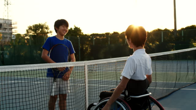 テニスの試合の後にセンターコートを話す2人の友人のslo moワイドショット - disabilitycollection点の映像素材/bロール