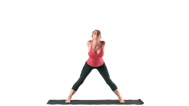 Wide shot of a white female doing yoga poses, on a mat Wide shot of a white female doing yoga poses, on a mat human joint stock videos & royalty-free footage