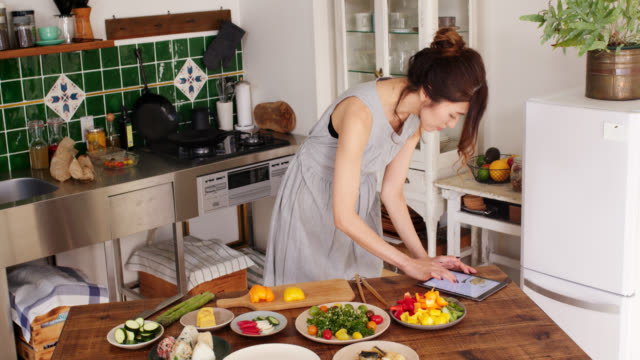 Wide shot of a young woman cooking using digital tablet for recipe