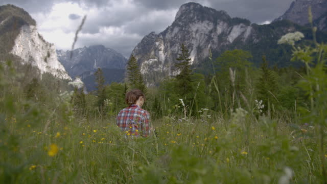 wide shot of a young woman sitting in tall grass in the mountains - эскапизм стоковые видео и кадры b-roll