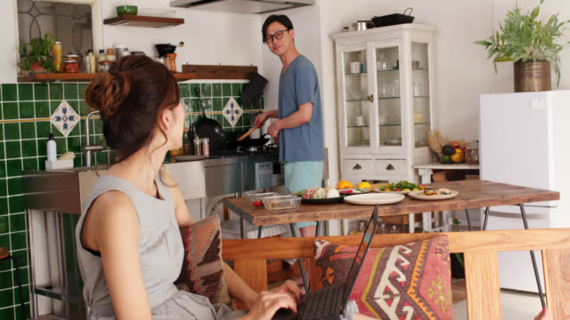 Wide shot of a young woman using a laptop and talking to her boyfriend whilst he is cooking in the background