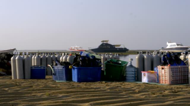 在海灘上潛水探險旅行所需的所有用品的廣拍 - 氧氣筒 個影片檔及 b 捲影像