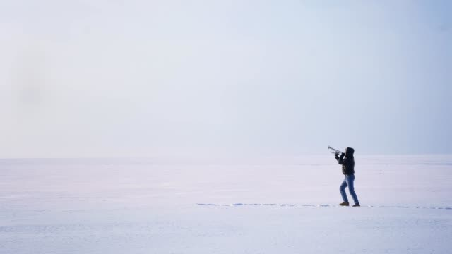 Wide shot of alone caucasian musician walking on snow and playing trumpet actively on frozen lake background.