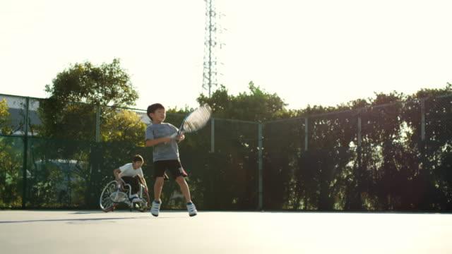 ダブルスをプレーするアダプティブテニス選手のワイドショット - disabilitycollection点の映像素材/bロール
