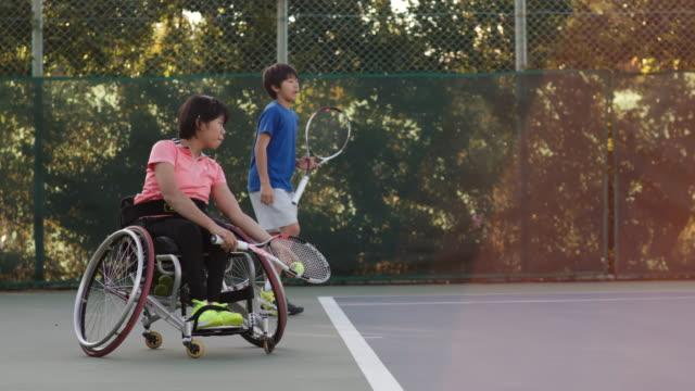 ダブルスをプレーするアダプティブテニス選手のslo moワイドショット - disabilitycollection点の映像素材/bロール