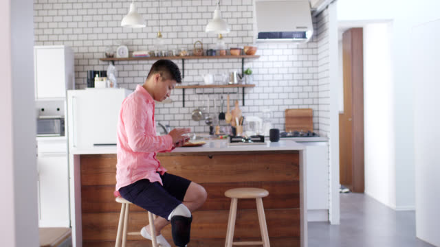 wide shot of an amputee male sitting in the kitchen using his smartphone - kitchen room video stock e b–roll