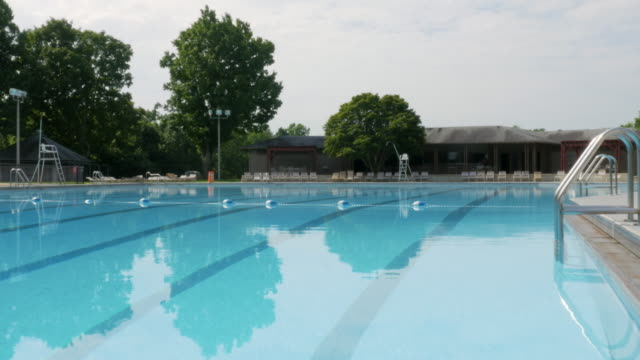 Wide Shot of an Empty Public Swimming Pool Wide shot of an empty public swimming pool. The outdoor olympic size pool at a park is deserted of swimmers. Trees reflect on the surface of the water. chlorine stock videos & royalty-free footage