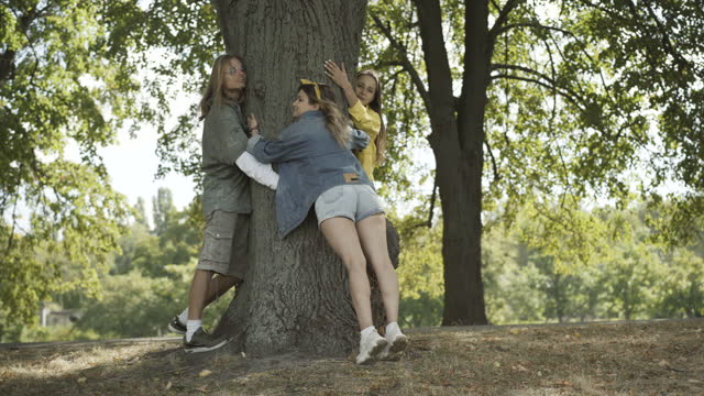 Wide shot of carefree Caucasian hippie man and women hugging tree trunk on sunny summer day outdoors. Happy relaxed friends enjoying nature and smiling. Leisure and counterculture of 1960s.