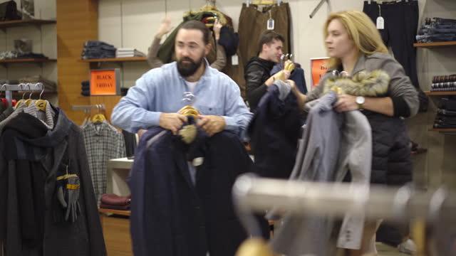 weitschuss von kaukasischen männern und frauen, die während des black friday-verkaufs im laden um kleidung kämpfen. männliche und weibliche kunden eilen, um waren mit dem besten preis zu kaufen. mode und lifestyle. - black friday stock-videos und b-roll-filmmaterial