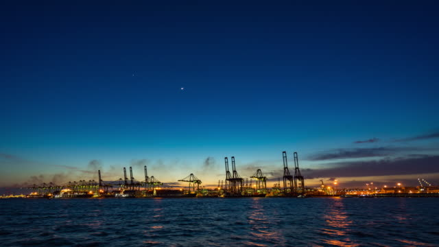 Wide Shot of Crane and Container Ship in Industrial Port at Night, Singapore, Day to Night Time Lapse Video