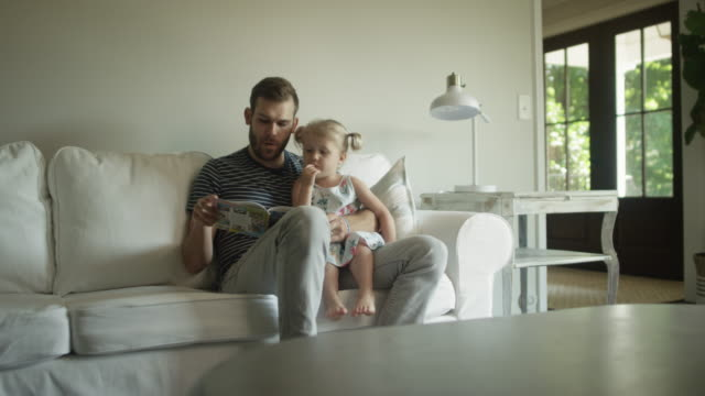 Wide shot of cute little blonde girl sitting on father's lap as he reads to her Wide shot of cute little blonde girl sitting on father's lap as he reads to her pigtails stock videos & royalty-free footage