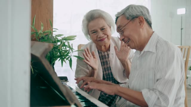 Wide shot of  happiness moment of  Asian senior couple singing and playing piano at home, 4K Resolution video
