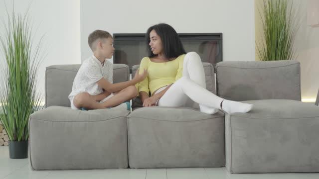 bred bild av glada afroamerikanska familjen sitter på mjuka fåtöljer hemma och chatta. positiv mamma och son prata och dela inomhus. lycklig kvinna och pojke tillbringar helgen tillsammans - parent talking to child bildbanksvideor och videomaterial från bakom kulisserna