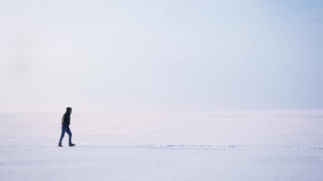 Wide shot of male silhouette in profile walking rightwards on snow.