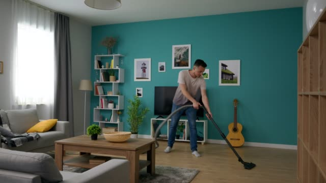 Wide shot of Man cleaning cozy apartment with vacuum cleaner video