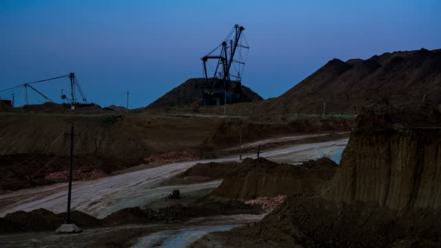 Wide shot of operating mine with dragline excavators loading ore in the background at dusk. Rear view of dump-truck passing by. Bauxite quarry. video