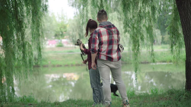 vídeos de stock e filmes b-roll de wide shot of positive couple hugging dog on lake shore and smiling. happy domestic pet with owners outdoors in the morning park - margem do lago