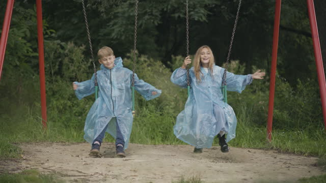 Wide shot of relaxed children in raincoats swinging on swings outdoors. Positive smiling Caucasian boy and girl enjoying rainy summer day. Concept of friendship and leisure