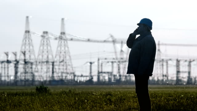 Wide shot of serious supervisor in hard hat talking on a smartphone during an energy substation inspection. video