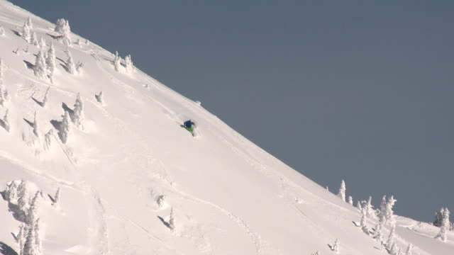 Wide shot of skiing powder on ridge-line with blue sky video