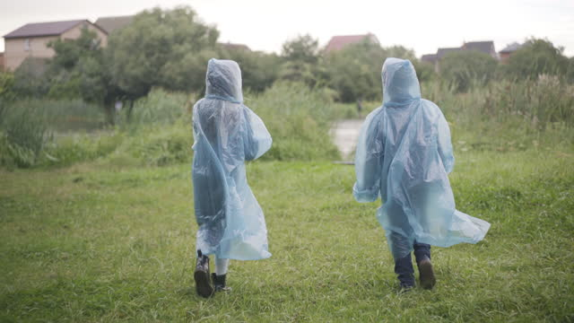 Wide shot of two children in raincoats walking along green summer meadow. Back view of joyful friendly Caucasian friends strolling and talking outdoors. Childhood and friendship