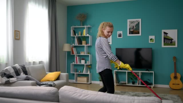 Wide shot of woman clean the floor in cozy apartment and dances video