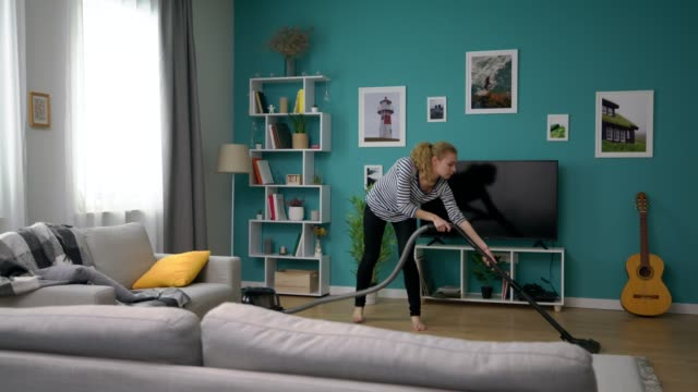 Wide shot of young beautiful girl vacuuming her cozy apartment video
