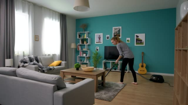 Wide shot of young beautiful woman vacuuming her cozy apartment video