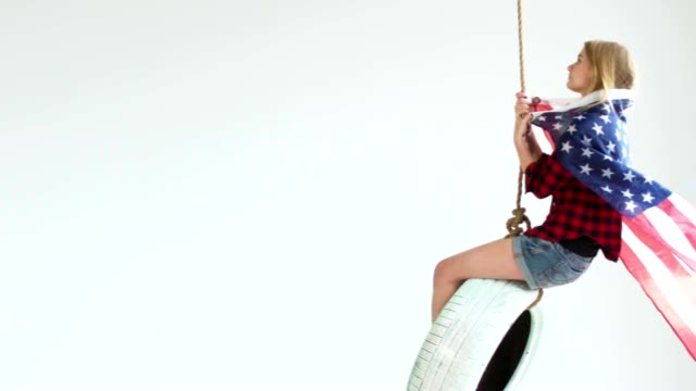 Wide shot of young Caucasian girl with waving American flag riding on a tire swing against white background video