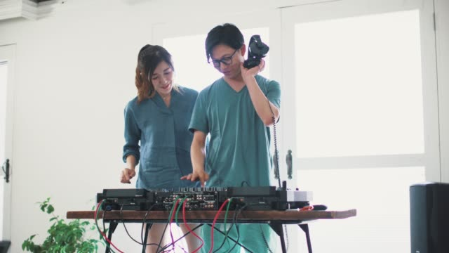 Wide shot of young couple enjoying hobbies at home