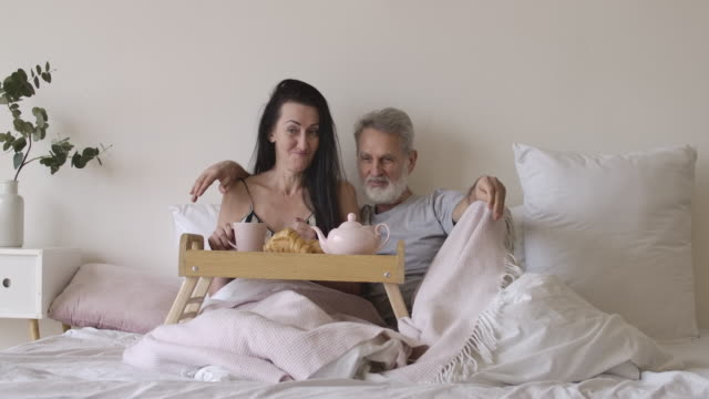 Wide shot portrait of happy senior Caucasian man and woman lying in bedroom with tea and croissants on bed tray. Smiling positive couple spending romantic morning at home. Cinema 4k ProRes HQ. Wide shot portrait of happy senior Caucasian man and woman lying in bedroom with tea and croissants on bed tray. Smiling positive couple spending romantic morning at home. Cinema 4k ProRes HQ. falling in love stock videos & royalty-free footage