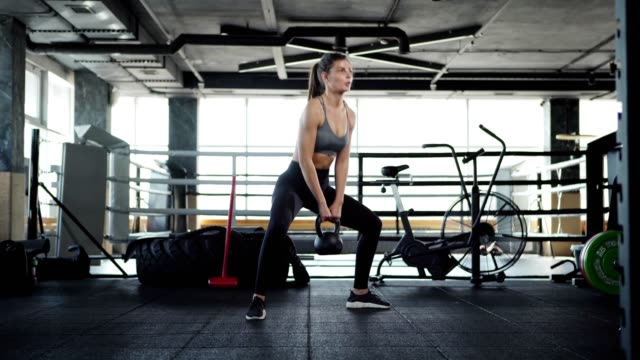 wide shot three quarter angle of fit young woman doing squats with kettlebell during cross training in gym - giria filmów i materiałów b-roll