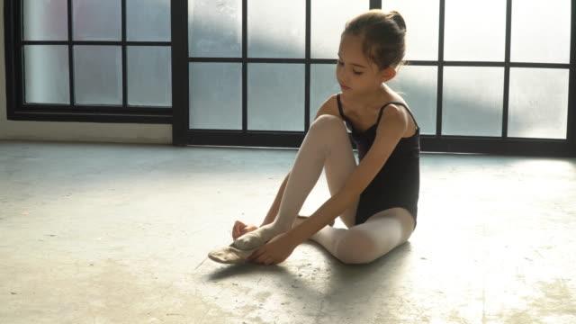 4K Wide shot young little child girl ballerina dancer in black leotard for dancing sitting on the floor in studio room wearing and tie ballet slipper shoe for private ballet dance practice.
